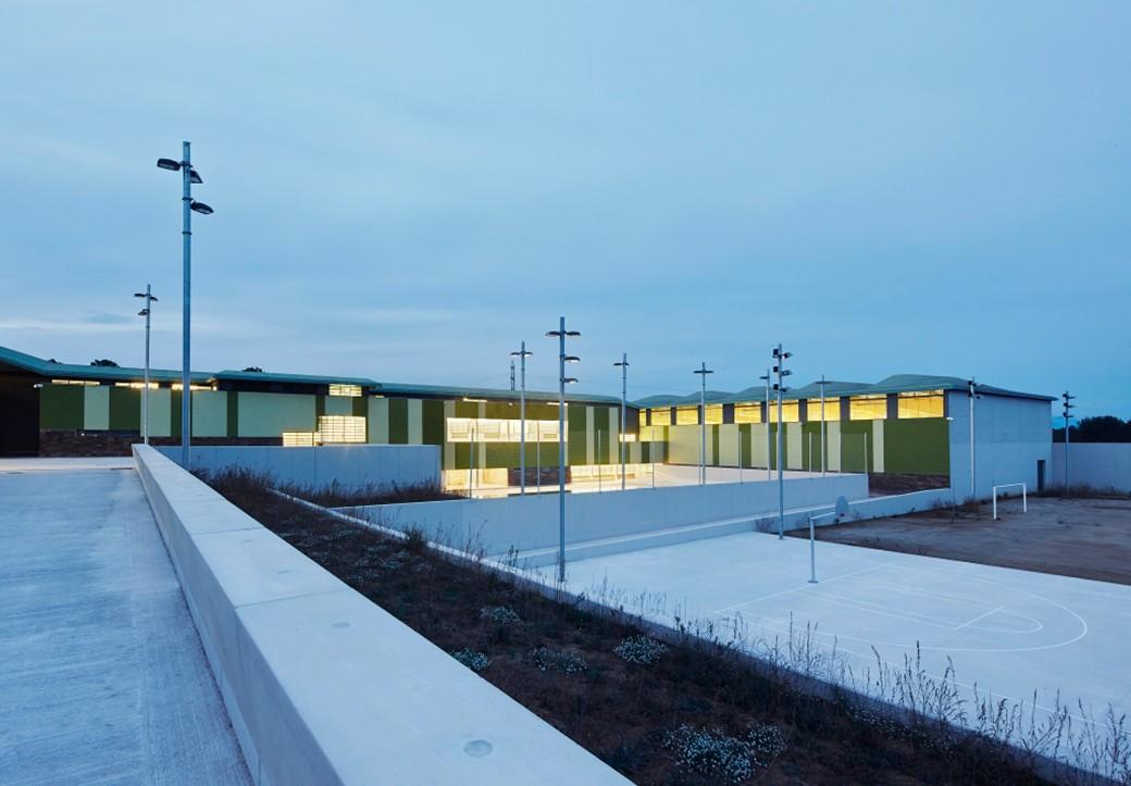 Atardecer en la prisión de Mas d'Enric. Puede verse la zona deportiva iluminada que es donde los reclusos hacen deporte.