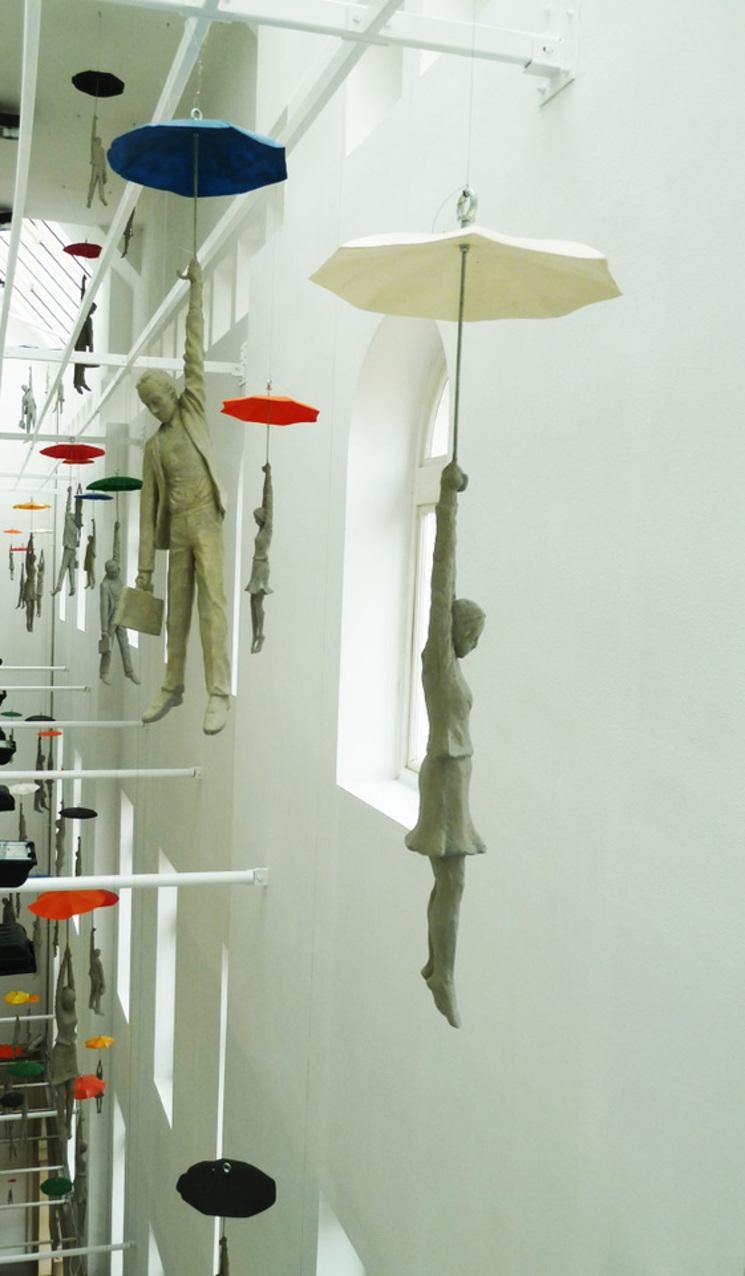 Docenas de esculturas colgando de un paraguas en un edificio de oficinas de Praga