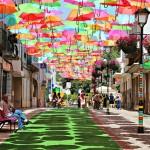Calle cubierta por paraguas de multiples colores en Portugal